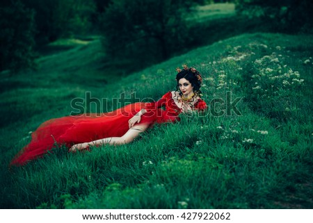 countess in a long red dress  is walking in a green forest full of branches, elf,  Princess in vintage dress, the queen of the forest,fashionable toning creative computer colors - stock photo