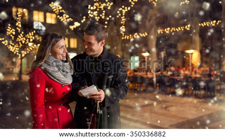 Couple in city street  with shopping list for Christmas - stock photo