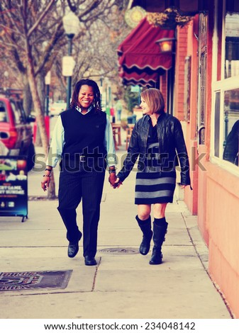 couple in love walking down a city street holding hands in a loving gesture toned with a retro vintage instagram filter effect - stock photo