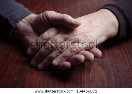 couple in their 60s holding hands together - stock photo
