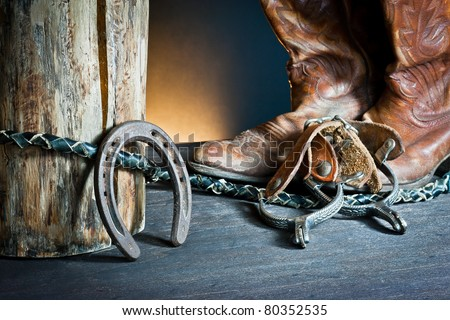 ,Cowboy boots,horseshoe,whip and spurs on wood, - stock photo