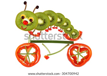 Creative food concept. Funny little caterpillar on a bicycle made from fruit and vegetables - stock photo