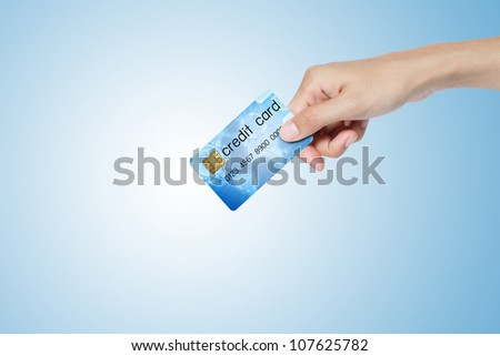 credit card hold on hand over blue background. - stock photo