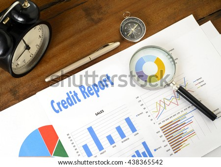 """Credit Report"" text on paper sheet with magnifying glass on chart clock,compass, pen, on wooden table - business, banking, finance and investment concept - stock photo"
