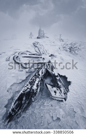 Cross snowbound in abandoned weather station in mountains. - stock photo