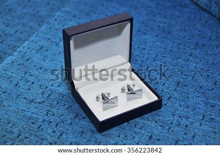 cufflink in blue box - stock photo