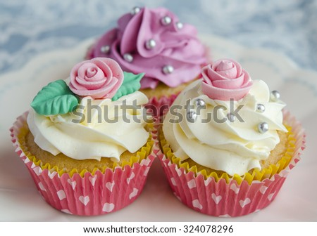 Cupcakes decorated with butter cream in various colors - stock photo