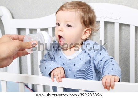 cute baby toddler drinking water from the feeding bottle