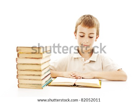 Cute boy studying and reading a book on his desk - stock photo