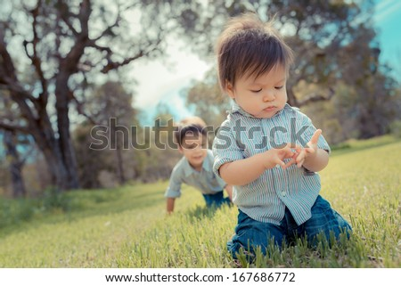 2 cute brothers playing outside in a grassy suburban park - stock photo