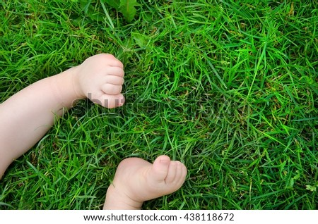 Cute child barefoot in the grass. View from above. Child concept.