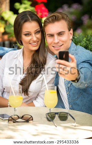 Cute couple taking selfie with smart phone  - stock photo
