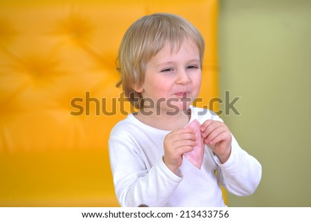 cute little boy in white tshirt eats sausage