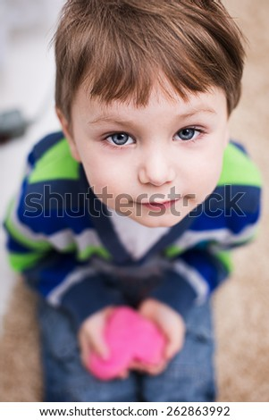 cute little boy sitting and holding  heart  - stock photo