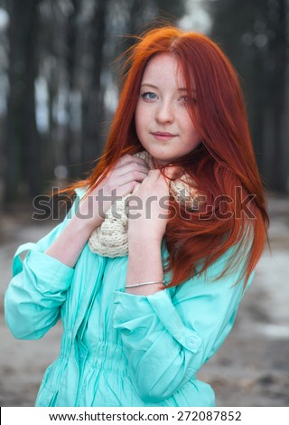 Cute red-haired girl in   park in spring day.  - stock photo