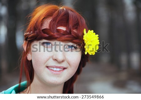 Cute red-haired girl in   park in spring day.