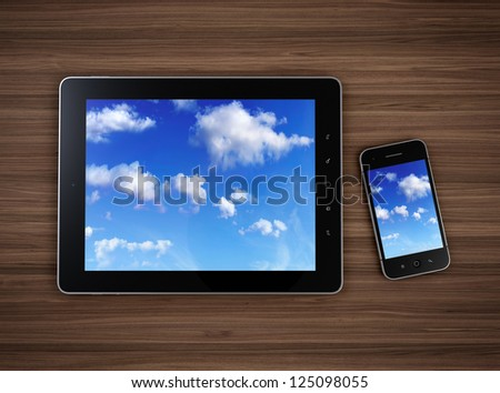 3d illustration of modern mobile devices on wooden table with cloudy sky on screen. Cloud computing concept.