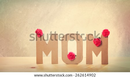 3D MOM Text with Fresh Carnation Flowers Standing on the Wooden Table with Light Brown Wall Background - stock photo