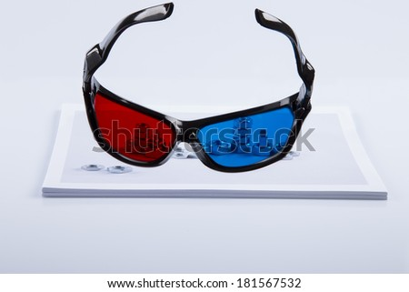 3D Print: black 3D anaglyphic Red Blue glasses and paper printed bolts. 3D Printers allow faster prototyping times transforming printing shapes in solid objects at very low costs in home laboratories  - stock photo