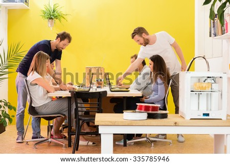 3D printer machine with products on counter with designers working in background at creative studio - stock photo