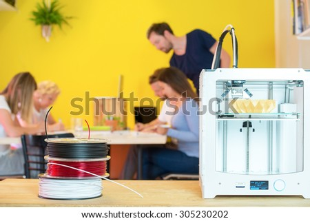 3D printer with product on counter with designers working in background at creative studio - stock photo