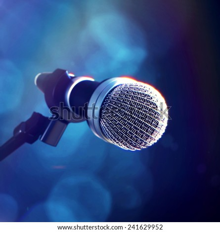 3d rendered illustration of close up of microphone on stage with blue bokeh blurred background
