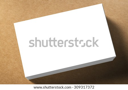 3d rendered stack of blank name cards on brown background - stock photo