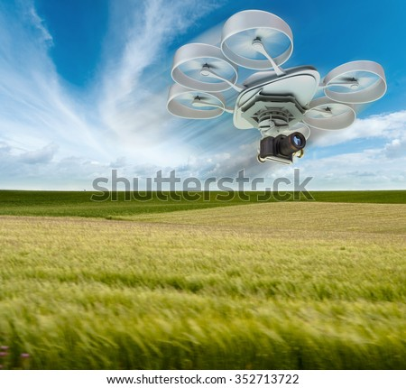 3D rendering of a drone equipped with a camera flying over green fields - stock photo