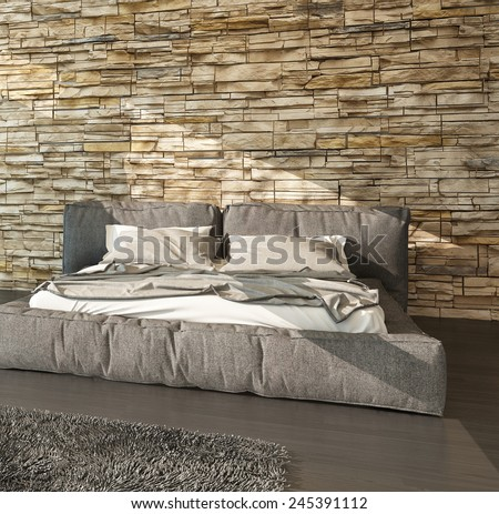 3D Rendering of Modern bed with padded upholstered headboard and footboard in shades of brown against a textured rough stone finish wall in a modern sunlit bedroom interior - stock photo