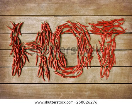3D rendering of the word hot formed with chili peppers on a wooden backgrounds - stock photo
