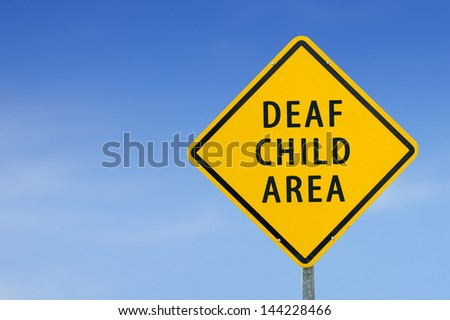 """DEAF CHILD AREA"" traffic sign with blue sky - stock photo"