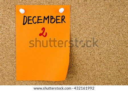 2 DECEMBER written on orange paper note pinned on cork board with white thumbtacks, copy space available - stock photo