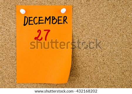 27 DECEMBER written on orange paper note pinned on cork board with white thumbtacks, copy space available - stock photo