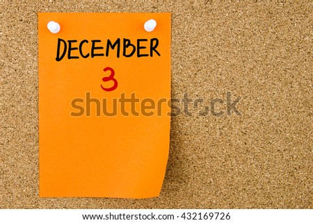 3 DECEMBER written on orange paper note pinned on cork board with white thumbtacks, copy space available - stock photo