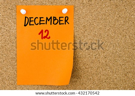 12 DECEMBER written on orange paper note pinned on cork board with white thumbtacks, copy space available - stock photo