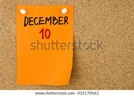 10 DECEMBER written on orange paper note pinned on cork board with white thumbtacks, copy space available - stock photo