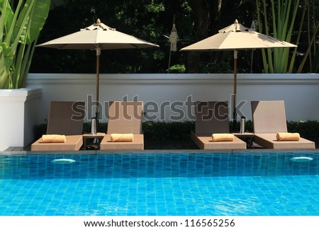 deck umbrella and swimming pool - stock photo