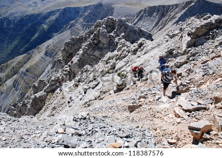 Deep mountain abyss with climbers in the distance - stock photo