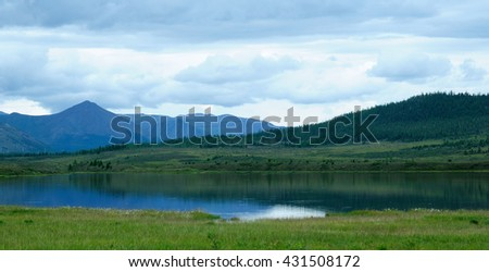 delicate haze of morning mist over the valley. hilly landscape, calm lake. Savannah, grassland . used toning of the photo  - stock photo