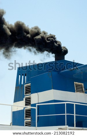departing ship with smoke emission and air pollution - stock photo