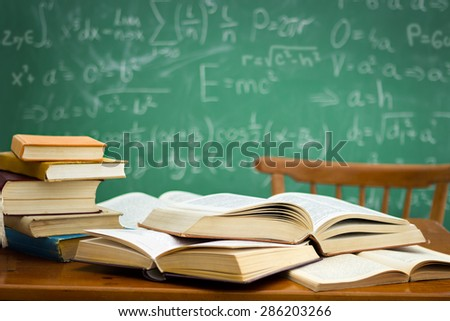 desk in a mess during learning with green blackboard in background  - stock photo
