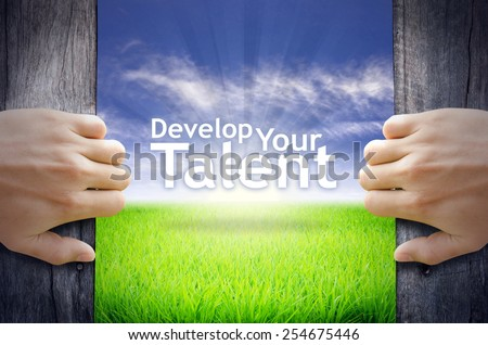 """Develop your Talent"" Motivational quotes. Hands opening a wooden door then found a texts floating among new world as green grass field, Blue sky and the Sunrise. - stock photo"