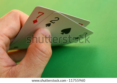 7 diamond and 2 spade (bad cards) in the hand on green background... - stock photo