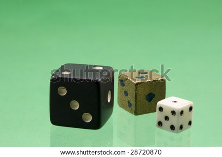 Dice of various sizes and colors are on the green background