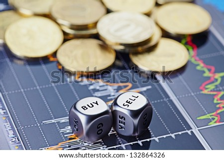 Dices cubes with the words SELL BUY and golden coins on financial chart as the background. Selective focus - stock photo