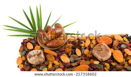 Different varieties mix of dried fruits and nuts and green leaf of palm isolated on white background. Selective focus is on the spoon with dates. - stock photo