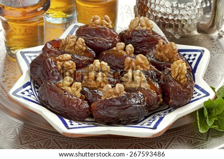 Dish with preserved ripe Medjool dates stuffed with walnuts for festive occasions - stock photo