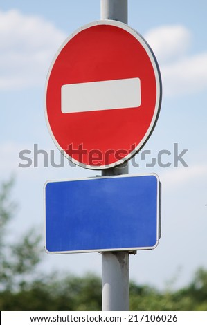 """Do not enter"" traffic sign with blue empty sign board underneath. - stock photo"