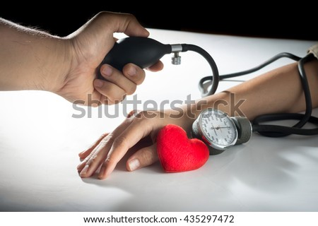 Doctor checking the blood pressure the patient. - stock photo