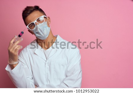 doctor medical mask with a syringe on a pink background, treatment, medicine
